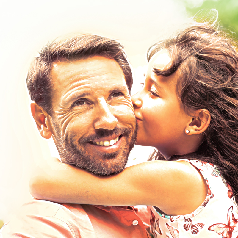 photo of a smiling man holding his daughter in his arms as she kisses his cheek, representing a successful family therapy result